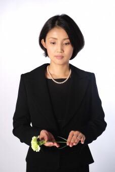 献花する喪服の女性